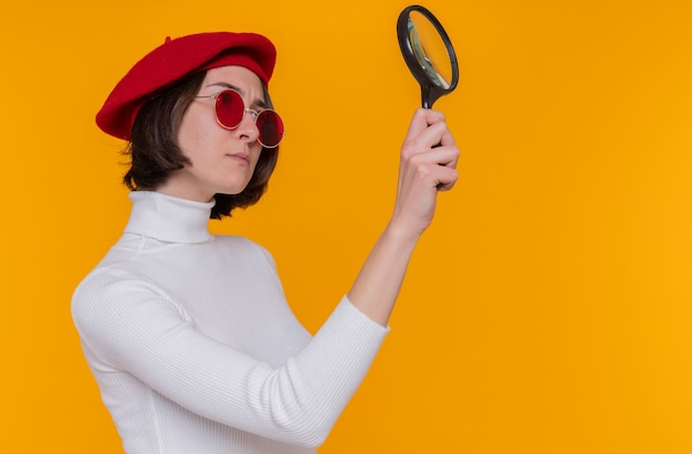 Jonge vrouw met kort haar in witte coltrui met baret en rode zonnebril opzij kijkend door dit vergrootglas met ernstig gezicht staande over oranje muur