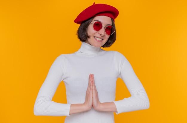Jonge vrouw met kort haar in witte coltrui met baret en rode zonnebril