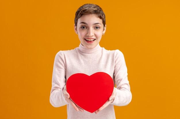 Jonge vrouw met kort haar met hart gemaakt van karton camera kijken gelukkig en positief glimlachend vrolijk valentijnsdag concept staande over oranje muur