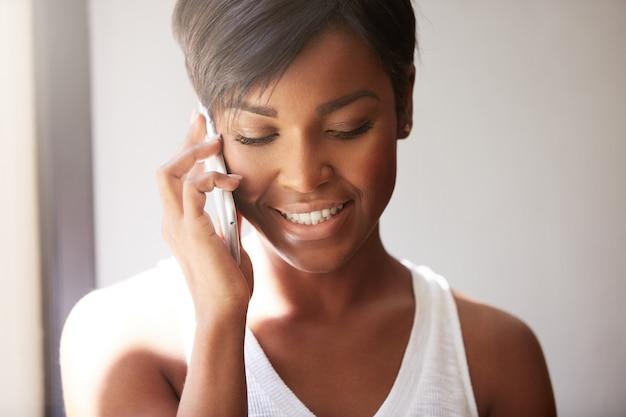 Jonge vrouw met kort haar praten aan de telefoon