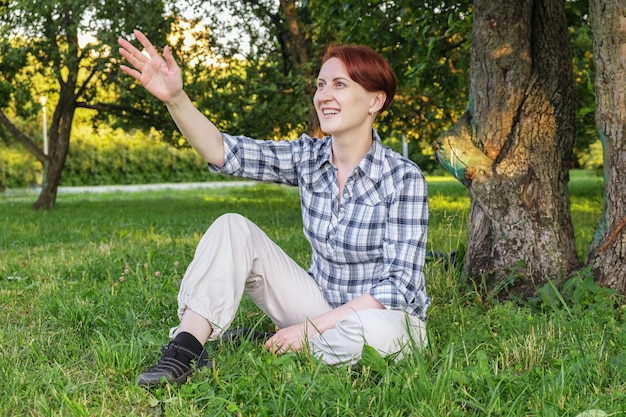 Jonge vrouw met kort haar zit op het gazon in het park en zwaait met haar hand ter begroeting
