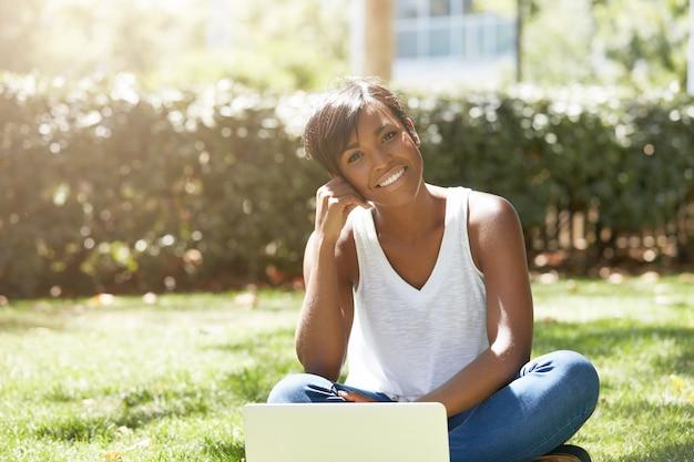 Jonge vrouw met kort haar, zittend in park