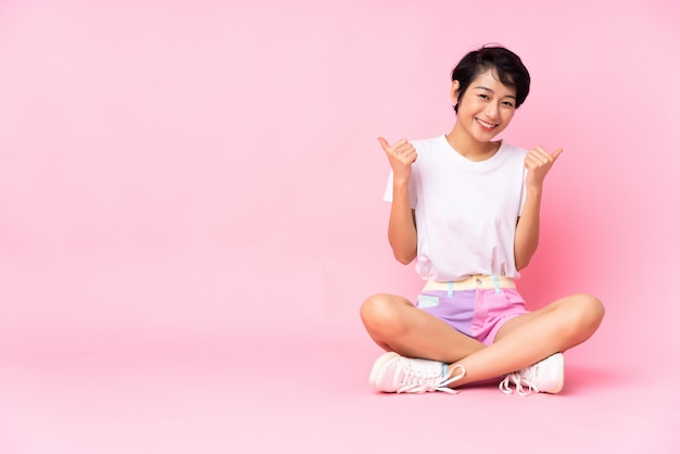 Jonge vrouw met kort haar zittend op de vloer over roze muur met thumbs up gebaar en lachend