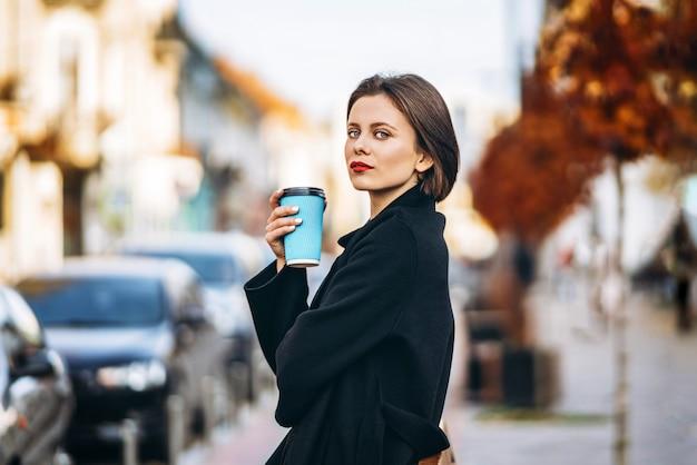 Jonge vrouw met kort kapsel en rode lippen, houdt een kopje koffie, slenterend door de straten van de stad. rondom zijn mensen en auto's.
