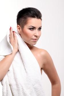Jonge vrouw met kort kapsel in handdoek