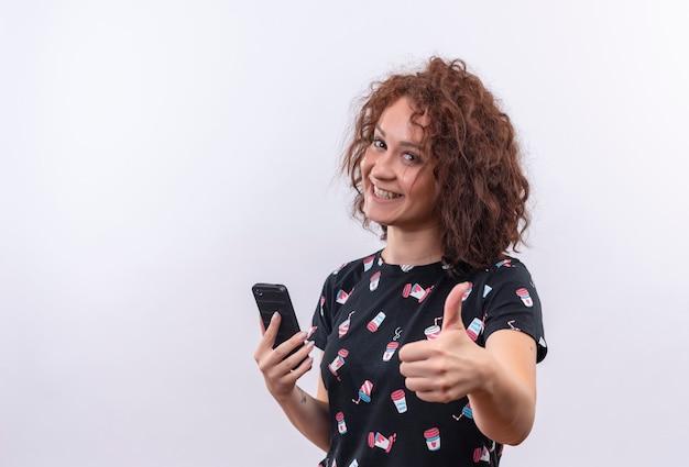 Jonge vrouw met kort krullend haar die smartphone glimlachen die vrolijk glimlachen tonen die omhoog duimen tonen die zich over witte muur bevinden
