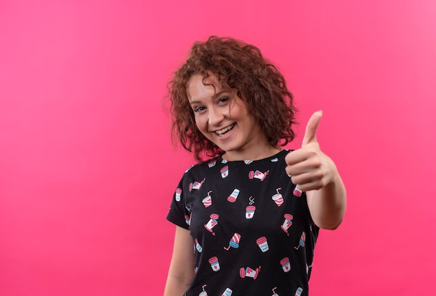 Jonge vrouw met kort krullend haar die vrolijk glimlachend duimen toont die zich over roze muur bevinden