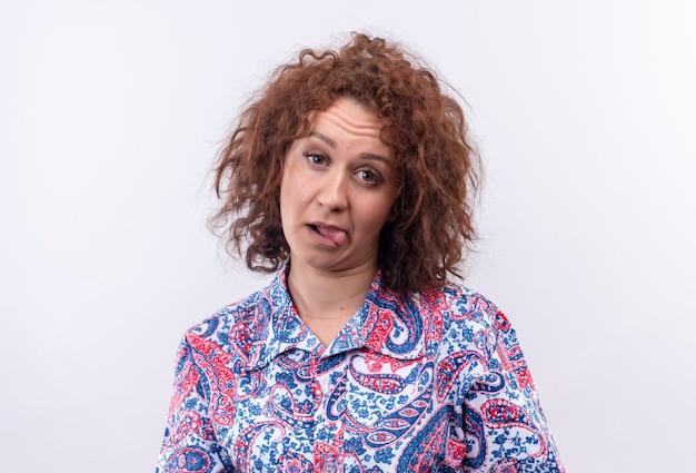 Jonge vrouw met kort krullend haar gehinderd in kleurrijke shirt tong uitsteekt