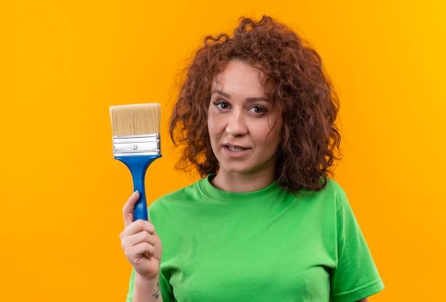 Jonge vrouw met kort krullend haar in de groene kwast van de t-shirtholding die zelfverzekerd status kijkt