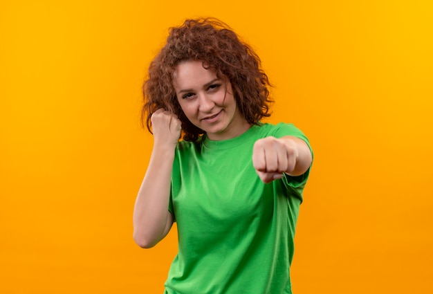 Jonge vrouw met kort krullend haar in groen t-shirt balde vuist die zich voordeed als bokser die zich over oranje muur bevindt