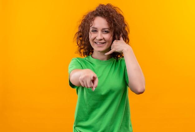 Jonge vrouw met kort krullend haar in groen t-shirt die bel me gebaar maken die met vinger aan voorzijde richten