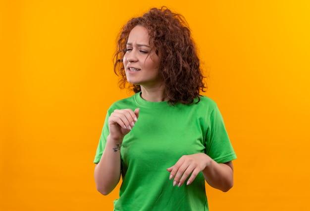 Jonge vrouw met kort krullend haar in groen t-shirt die defensiegebaar met weerzinwekkende uitdrukking maakt die zich over oranje muur bevindt