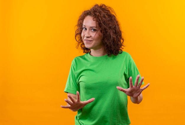 Jonge vrouw met kort krullend haar in groen t-shirt die haar handen uitstrekt als vertellend kom niet dichterbij staan