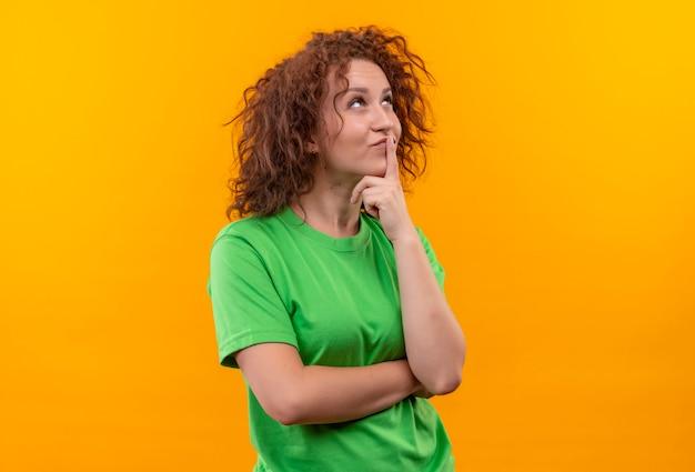 Jonge vrouw met kort krullend haar in groen t-shirt die met peinzende uitdrukking op gezicht kijken die zich over oranje muur bevinden denken