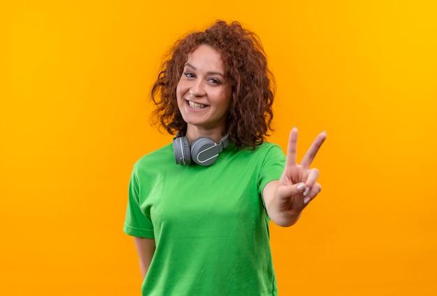 Jonge vrouw met kort krullend haar in groen t-shirt met hoofdtelefoons die overwinningsteken tonen die vrolijk over oranje muur glimlacht