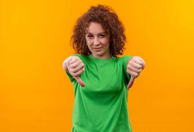Jonge vrouw met kort krullend haar in groen t-shirt op zoek ontevreden met duimen naar beneden staan
