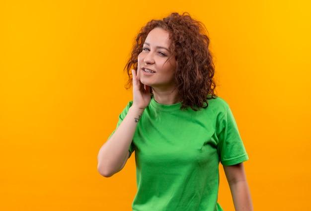 Jonge vrouw met kort krullend haar in groen t-shirt wat betreft haar wang die pijn voelt die zich over oranje muur bevindt