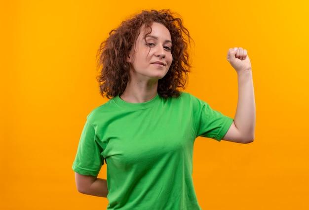 Jonge vrouw met kort krullend haar in groene t-shirt die vuist opheft die zich zelfverzekerd over oranje muur bevinden
