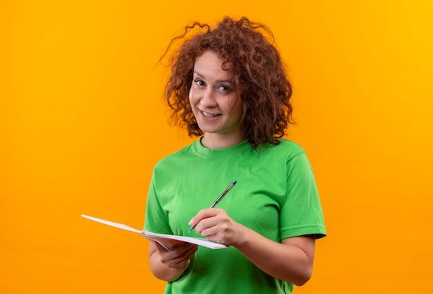 Jonge vrouw met kort krullend haar in het groene notitieboekje van de t-shirtholding en de pen die positief en gelukkig status glimlachen