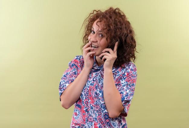 Jonge vrouw met kort krullend haar in kleurrijk overhemd blij en verrast tijdens het praten op mobiele telefoon glimlachend staande over groene muur