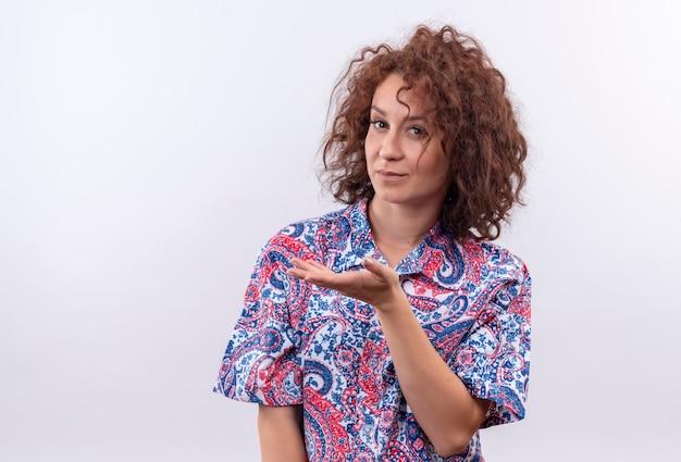 Jonge vrouw met kort krullend haar in kleurrijk overhemd dat arm opheft die verward kijkt als het stellen van een vraag die zich over witte muur bevindt