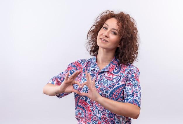 Jonge vrouw met kort krullend haar in kleurrijk overhemd die zelfverzekerd glimlachen tonen ok tekens met beide handen die hartgebaar maken die zich over witte muur bevinden