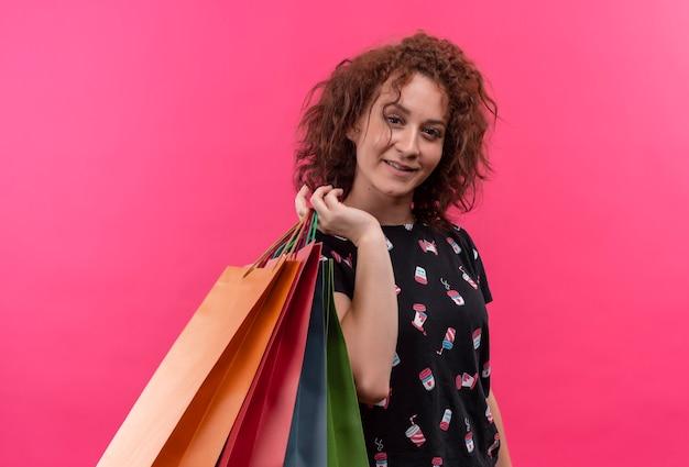 Jonge vrouw met kort krullend haar met papieren zakken glimlachend vrolijk blij en positief staande over roze muur