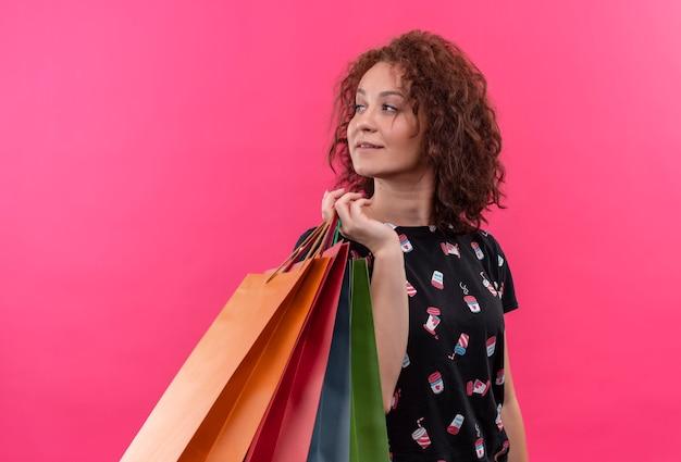 Jonge vrouw met kort krullend haar met papieren zakken opzij glimlachend vrolijk blij en positief staande over roze muur