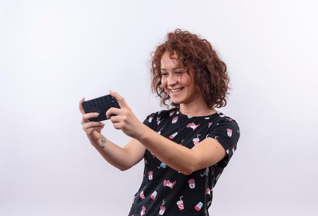 Jonge vrouw met kort krullend haar selfie met behulp van haar smartphone glimlachen