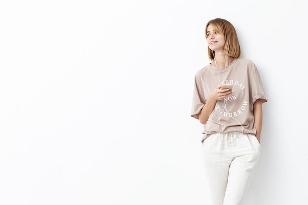 Jonge vrouw met kortgeknipt haar die vrijetijdskleding dragen die aan muziek luistert