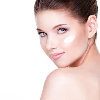 Jonge vrouw met kosmetische room op een schoon, fris gezicht. huid zorg concept