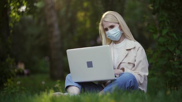 Jonge vrouw met krullen in een medisch masker werkt met behulp van een laptop in het park. werken op afstand tijdens quarantaine. buiten werk. 4k uhd