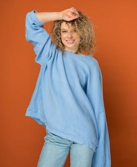 Jonge vrouw met krullend blond haar glimlachen
