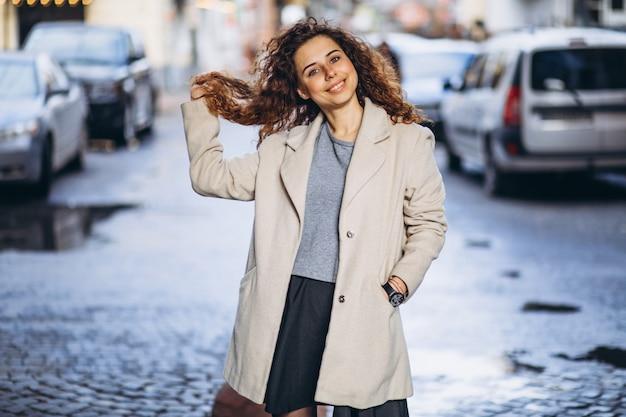Jonge vrouw met krullend haar buiten de straat