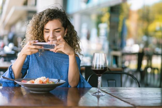 Jonge vrouw met krullend haar die foto's van haar eten maakt met een mobiele telefoon terwijl ze luncht in een restaurant.