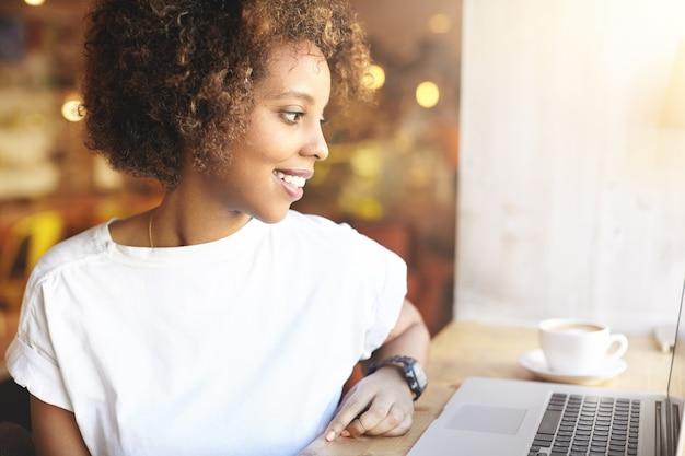 Jonge vrouw met krullend haar die laptop met behulp van