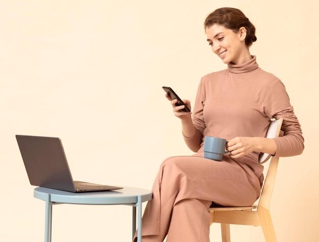 Jonge vrouw met krullend haar die mobiele telefoon met behulp van