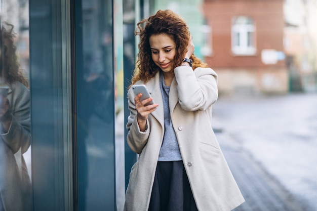 Jonge vrouw met krullend haar die telefoon met behulp van bij de straat