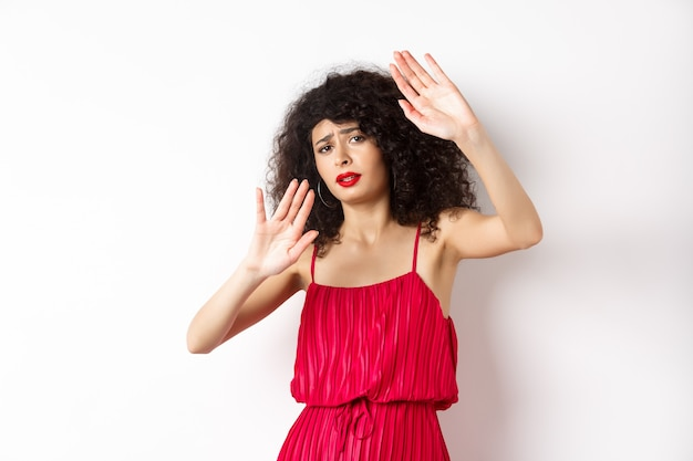 Jonge vrouw met krullend haar en rode jurk, die vraagt om te stoppen, iemand te blokkeren, de handen verdedigend op te heffen, zichzelf te beschermen, staande tegen een witte achtergrond.