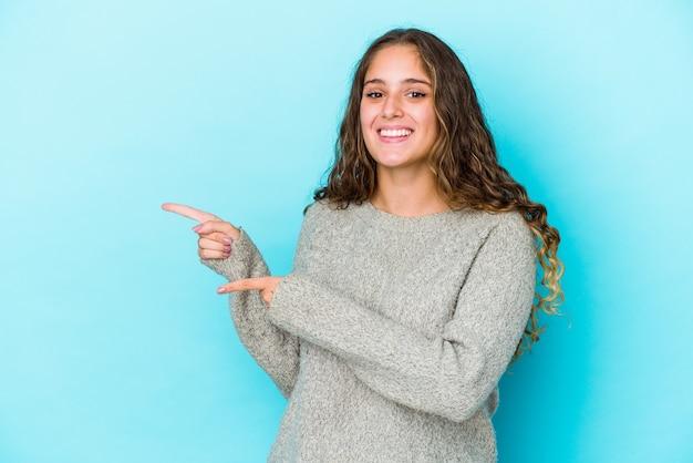 Jonge vrouw met krullend haar geïsoleerd opgewonden wijzend met wijsvingers weg