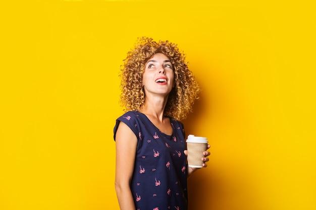 Jonge vrouw met krullend haar houdt een papieren beker opgezocht op een geel oppervlak