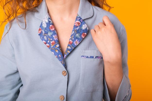 Jonge vrouw met krullend haar in blauwe huiskleding pyjama close-up