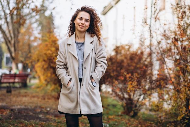 Jonge vrouw met krullend haar in park