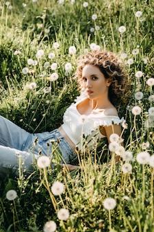 Jonge vrouw met krullend haar liggend in een weide met groen gras en paardebloemen