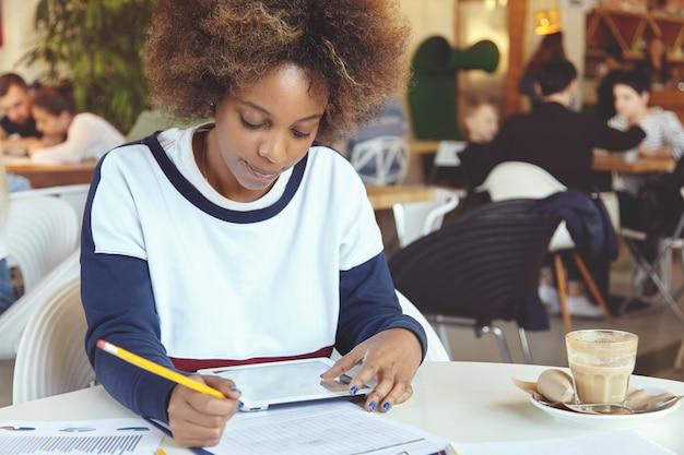 Jonge vrouw met krullend haar met behulp van tablet in café