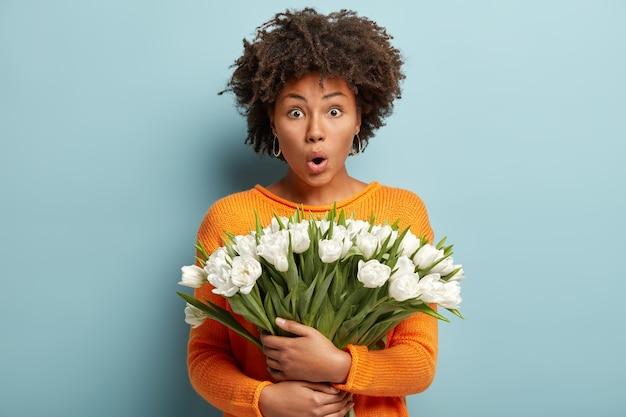 Jonge vrouw met krullend haar met boeket van witte bloemen