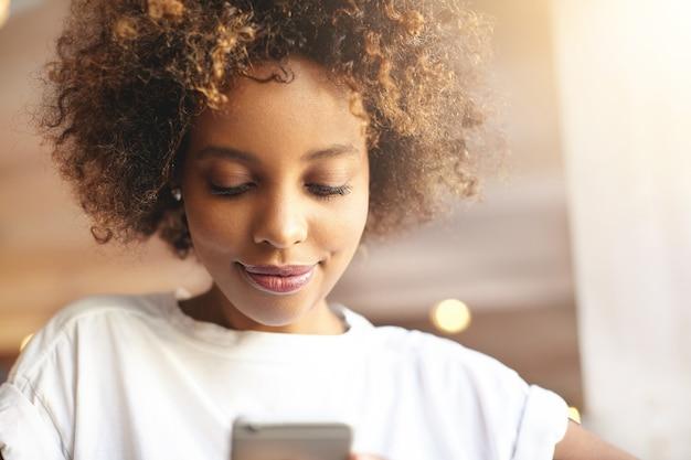 Jonge vrouw met krullend haar zitten in café met behulp van telefoon