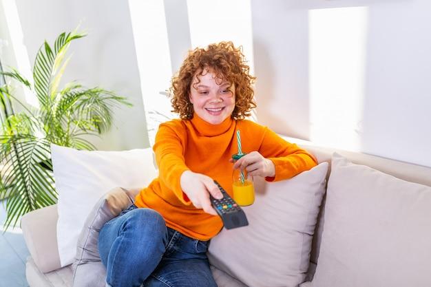 Jonge vrouw met krullend rood haar met afstandsbediening en tv kijken, kanalen wijzigen. leuk meisje die jus d'orange drinken en op tv in haar flat letten