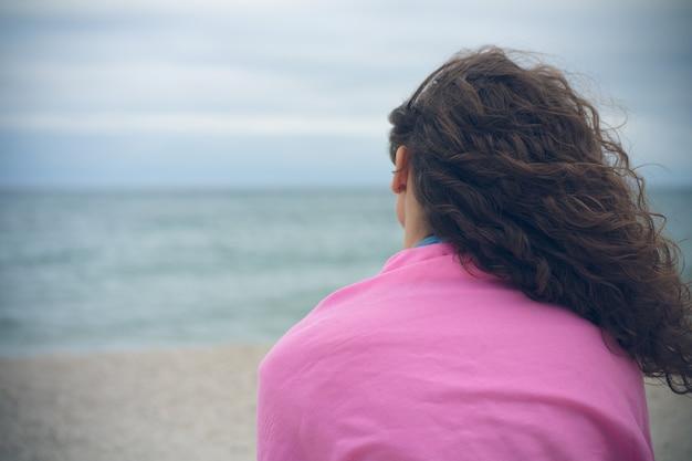 Jonge vrouw met krullende haarzitting alleen op het strand in bewolkt weer