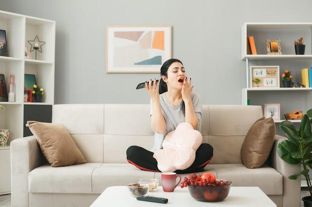Jonge vrouw met kussen met telefoon zittend op de bank achter de salontafel in de woonkamer
